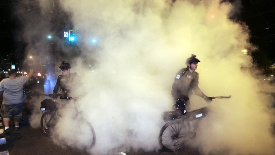 May 1, 2014: Police extinguish burning signs during May Day activities in Seattle.