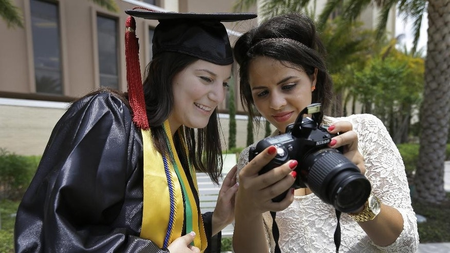 "April 29, 2014: University of South Florida graduating seniors Kyra Ciotti, 22, of Tampa, Fla., left, and Rita Sibaja, 24, of Winter Haven, Fla., look at photos that Rita took of Kyra in her cap and gown Tuesday, April 29, 2014, in Tampa, Fla. The university has banned all self portraits, also known as ""selfies,"" during their 2014 graduation exercises. (AP/Chris O'Meara)"