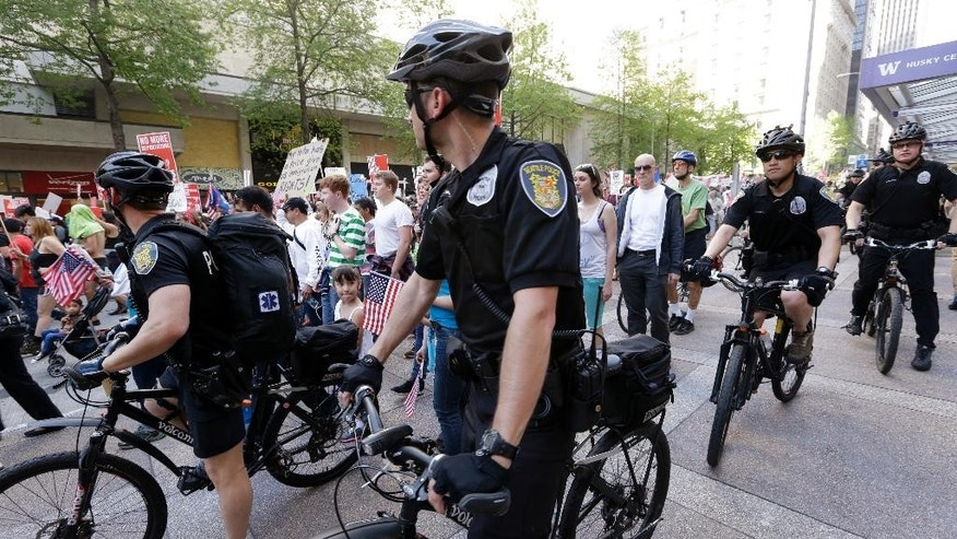 Seattle police officers escort demonstrators during a May Day march Thursday, May 1, 2014, in Seattle. Hundreds of people marched peacefully in support of immigrant and workers rights and a boost in the minimum wage in the afternoon demonstration. (AP Photo/Elaine Thompson)