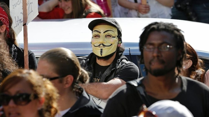 A demonstrator wears a Guy Fawkes mask as he stands with others at a May Day rally Thursday, May 1, 2014, in Seattle. Hundreds of people marched peacefully in support of immigrant and workers rights and a boost in the minimum wage in the afternoon demonstration. (AP Photo/Elaine Thompson)