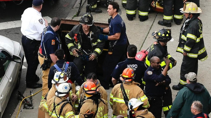 New York City firefighters emerge from a hatch in the sidewalk at 60th Street and Broadway after evacuating passengers from a subway train that derailed in the Queens borough of New York, Friday, May 2, 2014.  The express F train was bound for Manhattan and Brooklyn when it derailed at 10:40 a.m. about 1,200 feet (365 meters) south of the 65th Street station, according to the Metropolitan Transportation Authority. Dozens of firefighters and paramedics with stretchers converged on Broadway and 60th Street, where passengers calmly left the tunnel through the sidewalk opening. A few were treated on stretchers. (AP Photo/Julie Jacobson)
