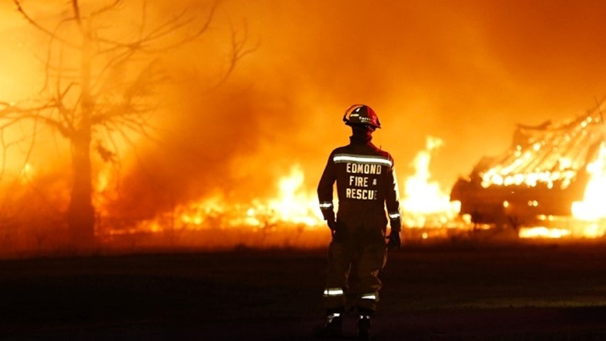May 4, 2014: An Edmond firefighter looks at a fire raging in a mobile home park near Prairie Grove Rd. and Douglas during Oklahoma wildfires in Logan County.  Firefighters worked through the night and into early Monday to battle the large wildfire that destroyed at least six homes and left at least one person dead after a controlled burn spread out of control in central Oklahoma.