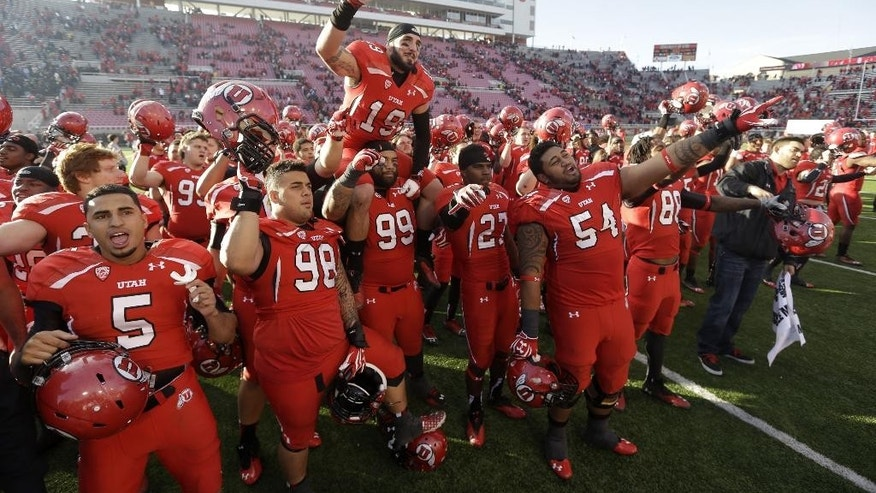 "FILE - In this Nov. 30, 2013, file photo, Utah players celebrate at the end of their NCAA college football game against Colorado, in Salt Lake City. University of Utah President David Pershing says he agrees it's time to consider some changes to the school fight song that some find sexist. Pershing announced Monday, May 5, 2014,  he's asking the Office of Student Affairs to oversee a committee that will weigh a ""modest update"" in the song, ""Utah Man."" (AP Photo/Rick Bowmer, File)"