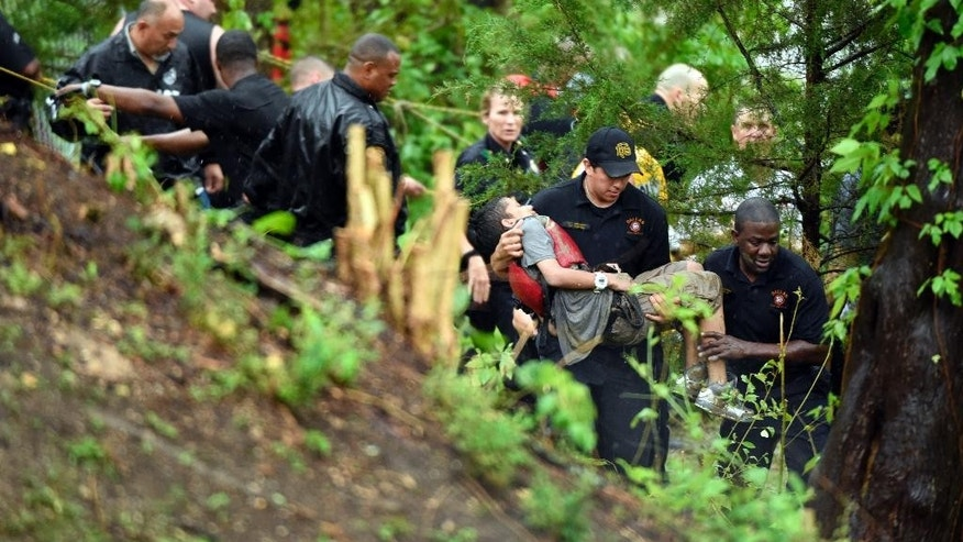 "A young boy is carried by a rescue worker as Dallas Police and Fire Department members take part in a high water rescue near Glen Oaks and Brook Valley in Dallas, Texas. on Thursday, May 8, 2014.  According to Dallas police, a group of students who were skipping school were trapped in a drainage tunnel  along a tributary of Woody Branch. Dallas Fire-Rescue spokesman Jason Evans said the five teenagers rescued from the water were skipping school. All five teens were taken to Children's Medical Center and were ""awake and alert."" (AP Photo/The Dallas Morning News, Michael Ainsworth)  MANDATORY CREDIT&#x3b; MAGS OUT&#x3b; TV OUT&#x3b; INTERNET USE BY AP MEMBERS ONLY&#x3b; NO SALES"