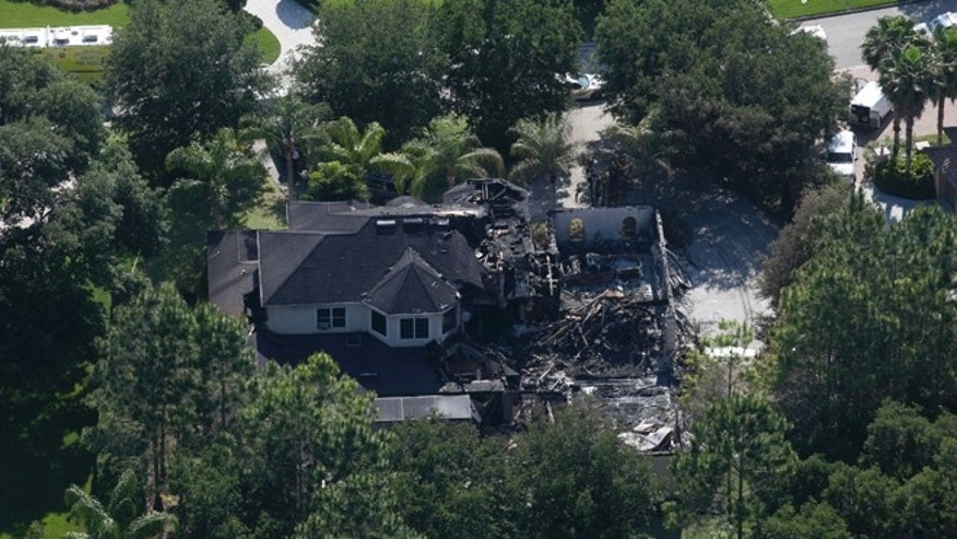 This aerial photo shows the burned out home on Thursday, May 8, 2014 in Tampa, Fla.  Authorities have said they think the fire at the five-bedroom home was intentionally set and that they found fireworks inside the home. Police have not said how the blaze started or who might be responsible. The home, which is owned by former tennis star James Blake, was engulfed in flames when firefighters responded Wednesday morning. Neighbors told police they heard explosions coming from it. Blake was renting the house to the a family and was not there at the time. (AP/The Tampa Bay Times, Eve Edelheit)