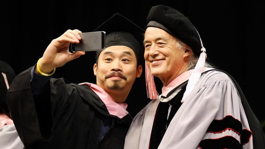 "Just before receiving his degree, Berklee College of Music graduate Wing-Ching Poon of Edmonton, Canada takes a ""selfie"" with former Led Zeppelin guitarist Jimmy Page, who received an Honorary Degree of Doctor of Music from the school during their commencement in Boston, Saturday, May 10. 2014. (AP Photo/Winslow Townson)"
