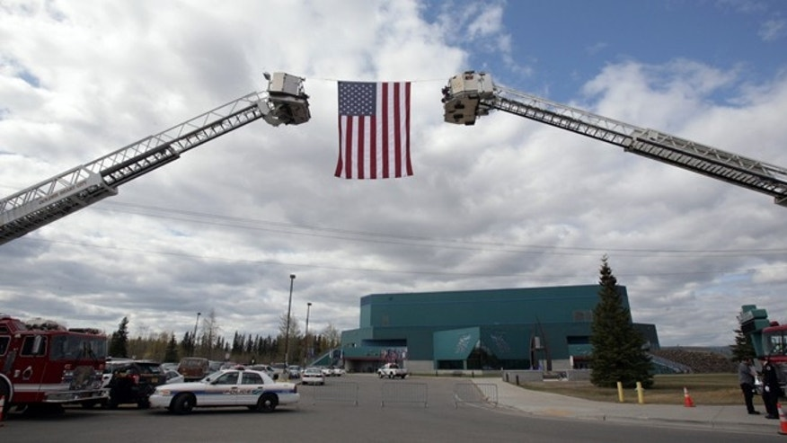 "May 10, 2014: The American Flag hangs from two fire department ladder trucks during the memorial service for Alaska State Trooper Sgt. Patrick ""Scott"" Johnson and Trooper Gabriel ""Gabe"" Rich at the Carlson Center in Fairbanks, Alaska."