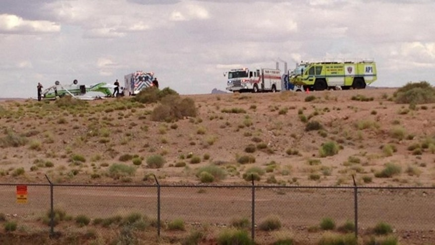 May 10, 2014: Authorities gather around the wreckage of a plane (at left, with green trim) in Page, Ariz. (MyFoxPhoenix)