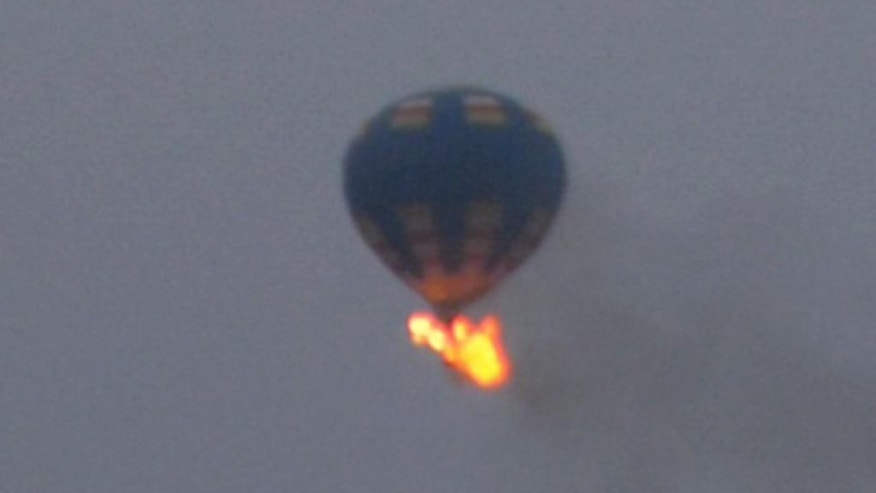 This photo provided by Nancy Johnson shows what authorities say is a hot-air balloon that was believed to have caught fire and crashed in Virginia, Friday, May 9, 2014. Virginia State Police received calls of the crash shortly before 8 p.m., police spokeswoman Corinne Geller told a news conference. Geller said a pilot and two passengers were believed to be on board, and that police believe it was the gondola that caught fire. (AP Photo/Nancy Johnson)