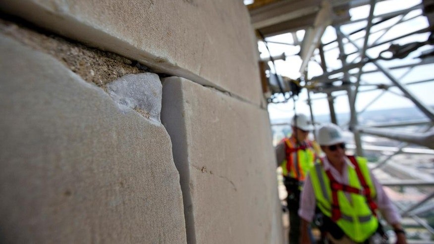 FILE - This June 2, 2013 file photo shows a damaged stone on the Washington Monument at the 491-foot level of the scaffolding surrounding the monument, in Washington. The monument, which sustained damage from an earthquake in August 2011, will re-open to the public on Monday, May 12, 2014. (AP Photo/Alex Brandon, File)