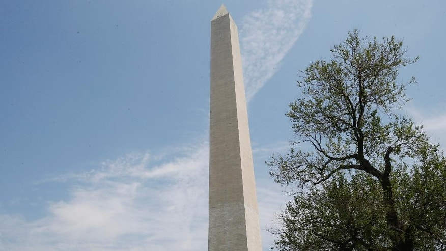 In this Friday, May 9, 2014 photo, visitors sit on the grass in front of the Washington Monument after the fencing which closed it off to the public during renovations was removed, in Washington. The monument, which sustained damage from an earthquake in August 2011, will re-open to the public on Monday, May 12, 2014. (AP Photo/Charles Dharapak)