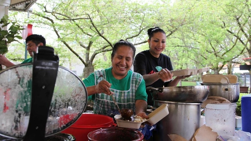 In this Tuesday, April 15, 2014 photo, Paula Asuncion, left, scoops traditional Oaxacan mole sauce onto a dish of tamales at the Lloyd Farmers Market, with her hired worked Julliana Rojas, right, helping,  in Portland, Oregon. Asuncion once worked in the fields, but after participating in a micro-business development program she now sells tamales at several farmers markets and runs a catering service. (AP Photo/Gosia Wozniacka)