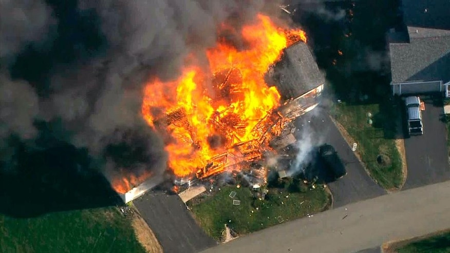 In this frame grab from television helicopter video, a home bursts into flames in Brentwood, N.H., Monday May 12, 2014.  Shots were fired just before the fire, which involved a police officer, according to the New Hampshire State Police. (AP Photo/WCVB-TV 5) TV OUT