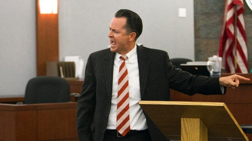 "Defense attorney Jeff Banks points to his client during opening statements during the trial for Jason Omar Griffith at the Regional Justice Center, Thursday, May 8, 2014, in Las Vegas . Griffith is accused of murdering Luxor ""Fantasy"" dancer Deborah Flores Narvaez in December 2010. A photo of Narvaez is displayed on the video monitor.  (AP Photo/The Las Vegas Sun, Steve Marcus) LAS VEGAS REVIEW-JOURNAL OUT"
