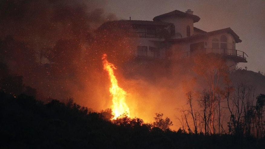 A wildfire burns near a home on Wednesday, May 14, 2014, in San Marcos, Calif. Flames engulfed suburban homes and shot up along canyon ridges in one of the worst of several blazes that broke out Wednesday in Southern California during a second day of a sweltering heat wave, taxing fire crews who fear the scattered fires mark only the beginning of a long wildfire season. (AP Photo)