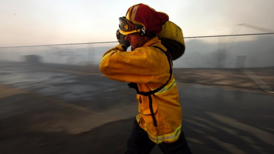 A Del Mar firefighter rolls up hose after a day fighting wildfires Wednesday, May 14, 2014, in Carlsbad, Calif. Flames engulfed suburban homes and shot up along canyon ridges in one of the worst of several blazes that broke out Wednesday in Southern California during a second day of a sweltering heat wave, taxing fire crews who fear the scattered fires mark only the beginning of a long wildfire season. (AP Photo)