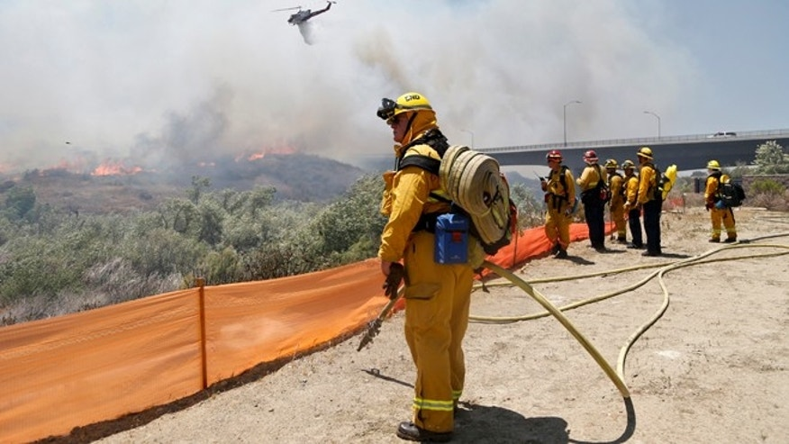 May 13, 2014: Firefighters watch from a ridge as a helicopter drops retardant on a out-of-control wildfire in San Diego.