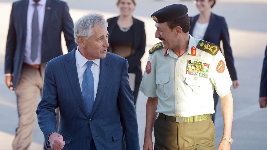 U.S. Secretary of Defense Chuck Hagel is welcomed by Jordan's Chairman of Defense Lieutenant General Mashal al-Zaben, right, upon his arrival at Marka International Airport in Amman, Jordan, Wednesday, May 14, 2014. Hagel is on a regional tour focusing on Iran's nuclear programm and Syria's civil war. (AP Photo/Mandel Ngan, Pool)