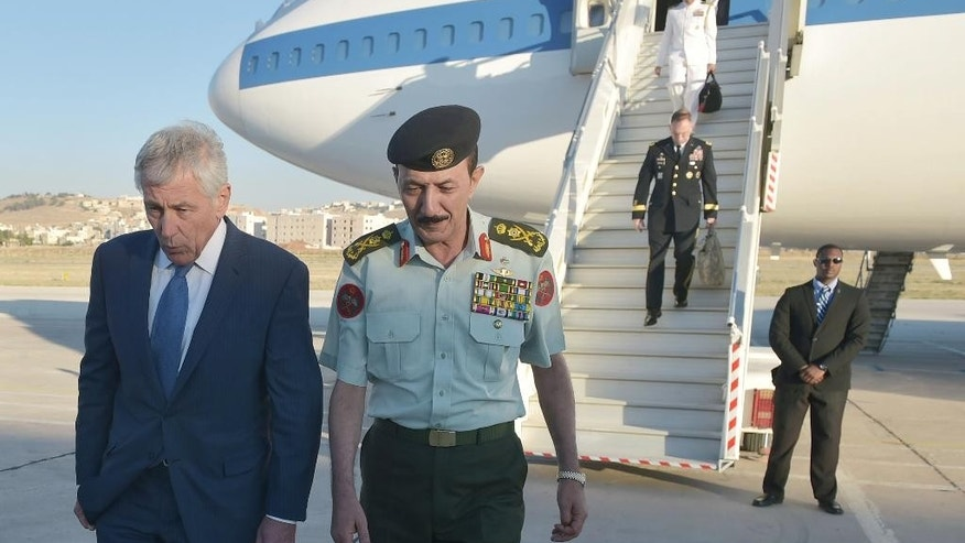 U.S. Secretary of Defense Chuck Hagel is welcomed by Jordan's Chairman of Defense Lieutenant General Mashal al-Zaben, right, upon his arrival at Marka International Airport in Amman on Wednesday, May 14, 2014. Hagel is on a regional tour focusing on Iran's nuclear programm and Syria's civil war. (AP Photo/Mandel Ngan, Pool)