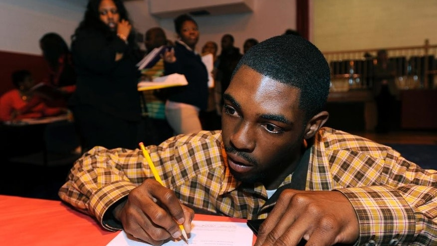 In this April 23, 2014 photo, Davon Tremble, of Detroit, fills out an application at a job fair at the Matrix Center in Detroit. The Labor Department reports the number of people who applied for unemployment benefits last week on Thursday, May 15, 2014. (AP Photo/The Detroit News, David Coates)