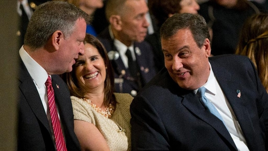 New York City Mayor Bill de Blasio, left, talks with New Jersey Gov. Chris Christie, right, and his wife Mary Pat Foster, before a ceremony at the National September 11 Memorial Museum, Thursday, May 15, 2014, in New York. The museum is a monument to how the Sept. 11 terror attacks shaped history, from its heart-wrenching artifacts to the underground space that houses them amid the remnants of the fallen twin towers' foundations. It also reflects the complexity of crafting a public understanding of the terrorist attacks and reconceiving ground zero.  (AP Photo/Carolyn Kaster)