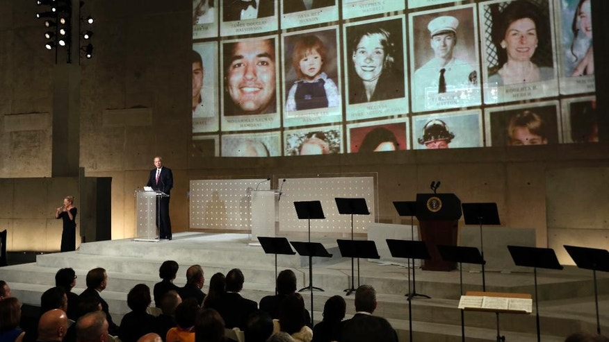 Former New York Gov. George Pataki speaks as photos of 9/11 victims are projected, during the dedication ceremony in Foundation Hall, of the National September 11 Memorial Museum, in New York, Thursday, May 15, 2014. (AP Photo/Richard Drew, Pool)