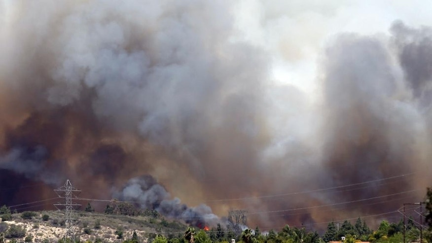 Wildfire climbs a canyon toward homes Wednesday, May 14, 2014, in Carlsbad, Calif. More wildfires broke out Wednesday in San Diego County — threatening homes in Carlsbad and forcing the evacuations of military housing and an elementary school at Camp Pendleton — as Southern California is in the grip of a heat wave. (AP Photo)