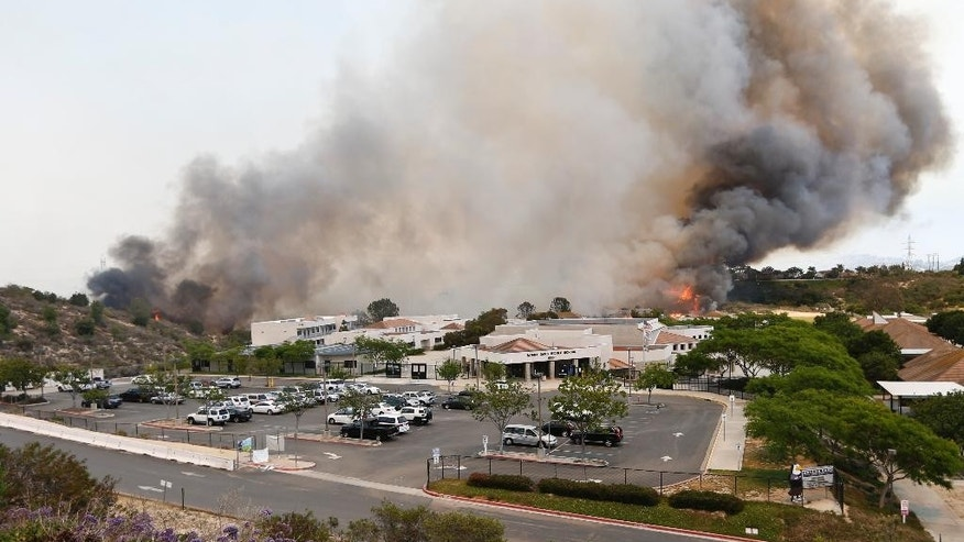 A wild fire burns toward a Aviara Oaks Middle School Wednesday, May 14, 2014, in Carlsbad, Calif.  Wind-driven flames are threatening homes in the coastal city of Carlsbad, where officials have sent mandatory evacuation notices to more than 11,000 homes and businesses. (AP Photo)