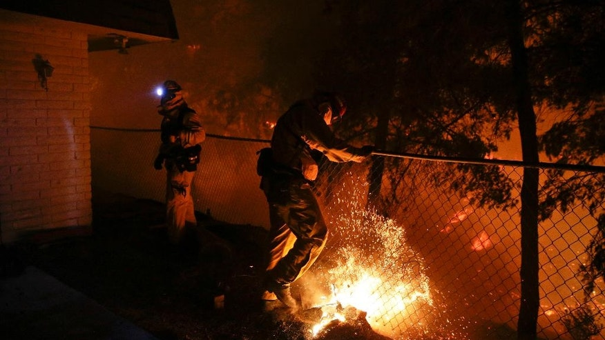 A firefighter puts out a small spot fire on Wednesday, May 14, 2014, in San Marcos, Calif. Flames engulfed suburban homes and shot up along canyon ridges in one of the worst of several blazes that broke out Wednesday in Southern California during a second day of a sweltering heat wave, taxing fire crews who fear the scattered fires mark only the beginning of a long wildfire season. (AP Photo)