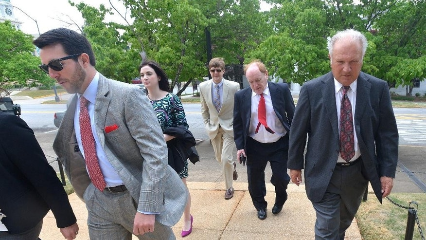 Former University of Georgia football coach Jim Donnan, right, heads into the Federal Courthouse on Wednesday, May 14, 2014, Athens, Ga.  Prosecutors say the 69-year-old and another man ran a fraudulent investment scheme from September 2007 to December 2010 through GLC Limited, a West Virginia-based company dealing in wholesale and closeout merchandise. Prosecutors say the pair promised high rates of return but paid investors with other investor money. (AP Photo/Athens Banner-Herald, Richard Hamm) MAGS OUT; MANDATORY CREDIT