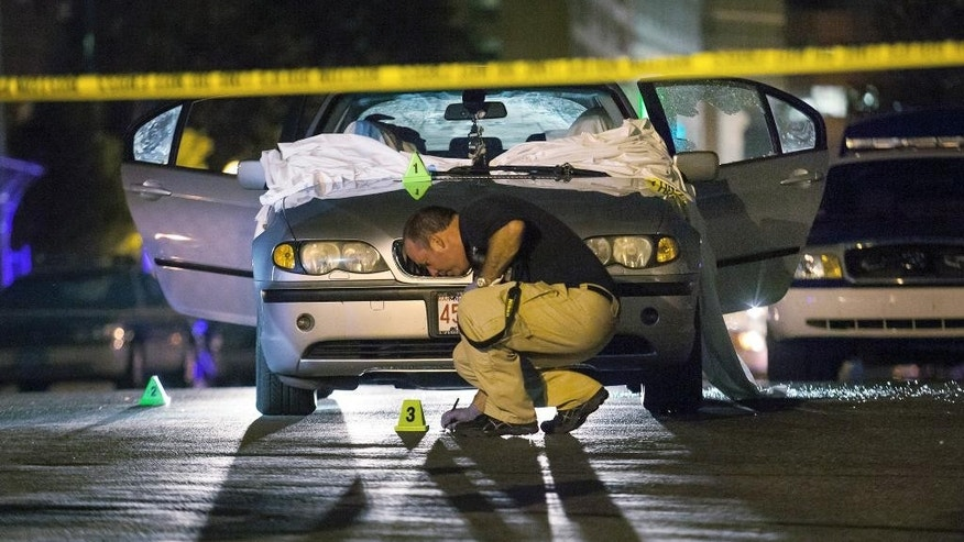 In this July 16, 2012 photo, Boston Police investigate a car in which Daniel de Abreu and Safiro Furtado were shot to death near the intersection of Herald Street and Shawmut Avenue in Boston. Prosecutors on Thursday, May 15, 2014 announced that former New England Patriots star Aaron Hernandez had been indicted on murder charges in their deaths. Hernandez is awaiting trial in a separate 2013 shooting death of Odin Lloyd, whose body was found in North Attleborough, Mass., not far from Hernandez's home. (AP photo/Courtney Sacco)