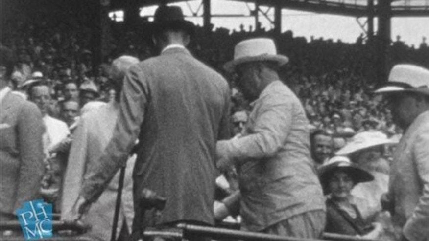 FILE: July 7, 1937: In this image taken from film shot by former Major League Baseball player Jimmie DeShong and acquired by the Pennsylvania Historical & Museum Commission, President Franklin D. Roosevelt, center right, walks to his seat with the aid of an assistant at the Major League Baseball All-Star game at Griffith Stadium in Washington.