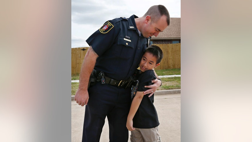 In this May 13, 2014 photo, Moore police officer Travis Muehlenweg, left, hugs Kai Heuangpraseuth, as they meet in Moore, Okla. Muehlenweg was photographed with Heuangpraseuth as he helped pull him from the rubble of Plaza Towers Elementary school following the May 20, 2013, tornado. Heuagpraseuth's mother, Jacalyn Russell, said that her son has wanted to meet Muehlenweg for nearly a year. (AP Photo/Sue Ogrocki)