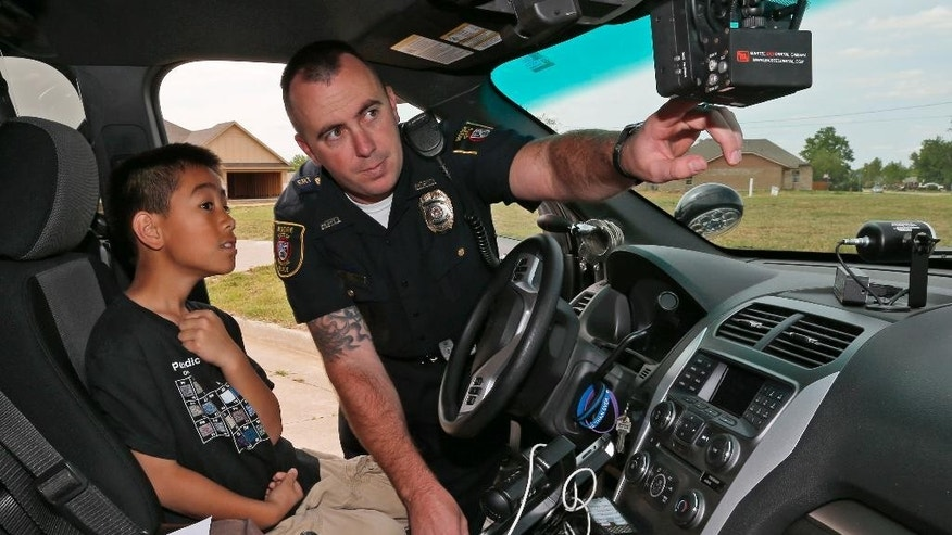 In this May 13, 2014 photo, Moore Police Officer Travis Muehlenweg, right, shows 10-year-old Kai Heuangpraseuth, left, the interior of his police vehicle in Moore, Okla. Muehlenweg, a four-year veteran helped pull the third grader from under a wall at Plaza Towers Elementary after a tornado hit the town on May 20, 2013. (AP Photo/Sue Ogrocki)