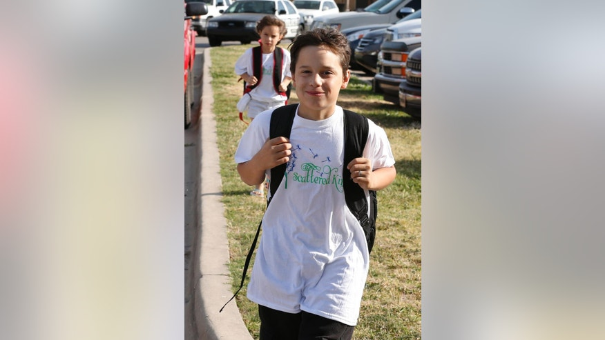 Xavier Delgado, front, and his sister, Haley Delgado, rear, arrive for the start of school at the temporary site for Plaza Towers Elementary school in Moore, Okla., Tuesday, May 20, 2014, one year after the May 20, 2013 tornado destroyed Plaza Towers school, leaving Xavier Delgado and other third graders trapped in the rubble. (AP Photo/Sue Ogrocki)