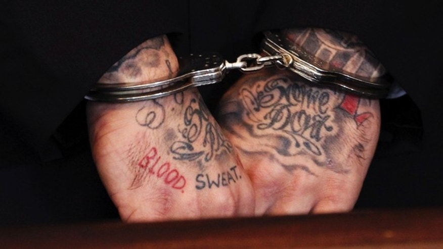 FILE 2013: The words 'blood' and 'sweat' are seen tattooed on the hands of former NFL New England Patriots tight end Aaron Hernandez, as he appears in court for a motion hearing in Attleborough, Mass.