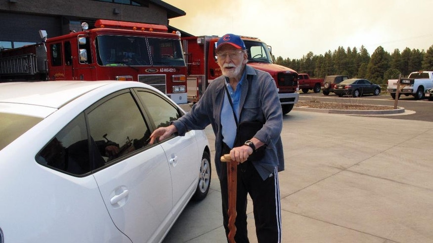 Dick Summitt, of Kachina Village in northern Arizona, leaves a community meeting on Wednesday, May 21, 2014 where authorities told residents to prepare to evacuate because of a wildfire. Hundreds of firefighters poured into the area to battle the wind-whipped blaze. (AP Photo/Felicia Fonseca)