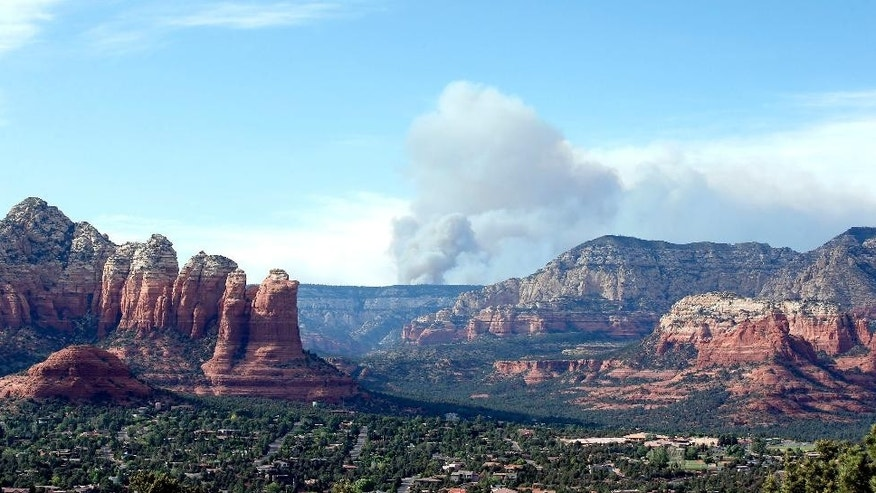 Smoke rises from the Slide Fire as it burns up Oak Creek Canyon on Thursday, May 22, 2014, in Sedona, Ariz.  The fire has burned approximately 4,800 acres. (AP Photo/Ross D. Franklin)