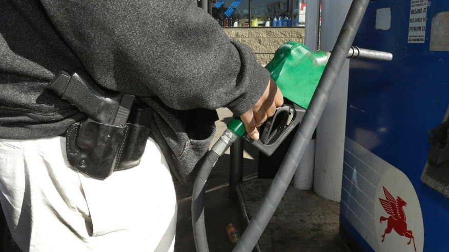 In a photo from April 9, 2014, Greg Champion wears a gun while pumping gas in Detroit. To avoid becoming a carjacking victim, Champion wears a handgun on his hip whenever hes pumping gas. Through May 19, Detroit has recorded 191 carjackings in 2014. (AP/Carlos Osorio)