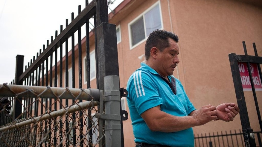 Ricardo Ledesma, who said he was a friend of kidnapping suspect Isidro Garcia, pauses for a moment while talking  to reporters in front of an apartment building where Garcia lived on Thursday, May 22, 2014, in Bell Gardens, Calif. A California woman who says she was kidnapped a decade ago by her mother's boyfriend lived a seemingly ordinary life with her alleged captor year after year, but was too scared to go to authorities until she recently reunited with her mother, police said Thursday. (AP Photo/Jae C. Hong)