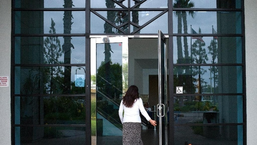 A woman enters a Los Angeles County Department of Children and Family Services building, where kidnapping suspect Isidro Garcia worked as a janitor, on Thursday, May 22, 2014, in Commerce, Calif. A California woman who says she was kidnapped a decade ago by her mother's boyfriend lived a seemingly ordinary life with her alleged captor year after year, but was too scared to go to authorities until she recently reunited with her mother, police said Thursday. (AP Photo/Jae C. Hong)