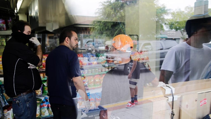 IV Deli Mart owner Michael Hassan, second from left, cleans up with his employees as onlookers gather outside the store where part of Friday night's mass shooting took place by a drive-by shooter, on Saturday, May 24, 2014, in Isla Vista, Calif. Alan Shifman, a lawyer who represents Hollywood director Peter Rodger, says the family believes Rodger's son, Elliot Rodger, was the gunman who went on the shooting rampage near the University of California at Santa Barbara. (AP Photo/Jae C. Hong)