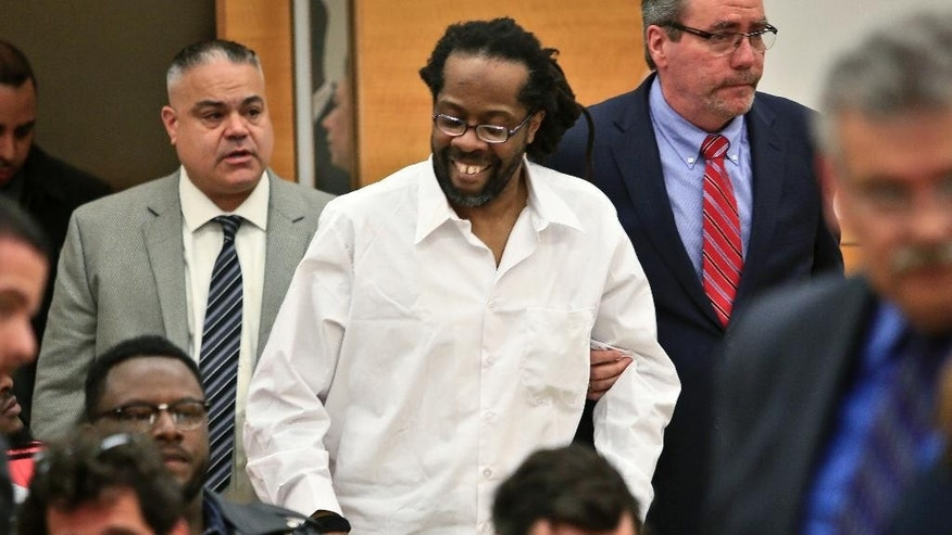 FILE- In this May 6, 2014 file photo, Robert Hill, center, smiles as he is escorted into Brooklyn Supreme Court in New York. Hill and his half-brothers Alvena Jennette and Darryl Austin were exonerated in a decades-old conviction investigated by retired homicide detective Louis Scarcella, who has had some of his tactics have come into question. The Brooklyn District Attorney's Conviction Review Unit is currently re-examining more than cases that Scarcella worked on. (AP Photo/Bebeto Matthews, File)