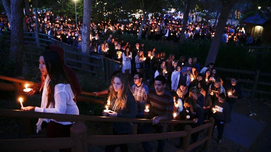 People gather at a park for a candlelight vigil to honor the victims of Friday night's mass shooting on Saturday, May 24, 2014, in Isla Vista, Calif. Sheriff's officials said Elliot Rodger, 22, went on a rampage near the University of California, Santa Barbara, stabbing three people to death at his apartment before shooting and killing three more in a crime spree through a nearby neighborhood. (AP Photo/Jae C. Hong)