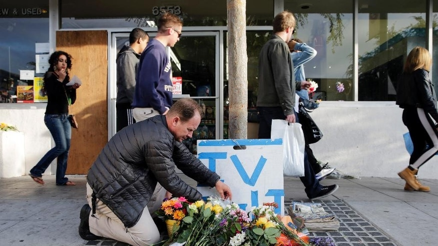 Stephen Nichols arranges flowers left in front of IV Deli Mart, where part of Friday night's mass shooting took place by a drive-by shooter, on Saturday, May 24, 2014, in Isla Vista, Calif. Sheriff's officials say Elliot Rodger, 22, went on a rampage near the University of California, Santa Barbara, stabbing three people to death at his apartment before shooting and killing three more in a crime spree through a nearby neighborhood. (AP Photo/Jae C. Hong)