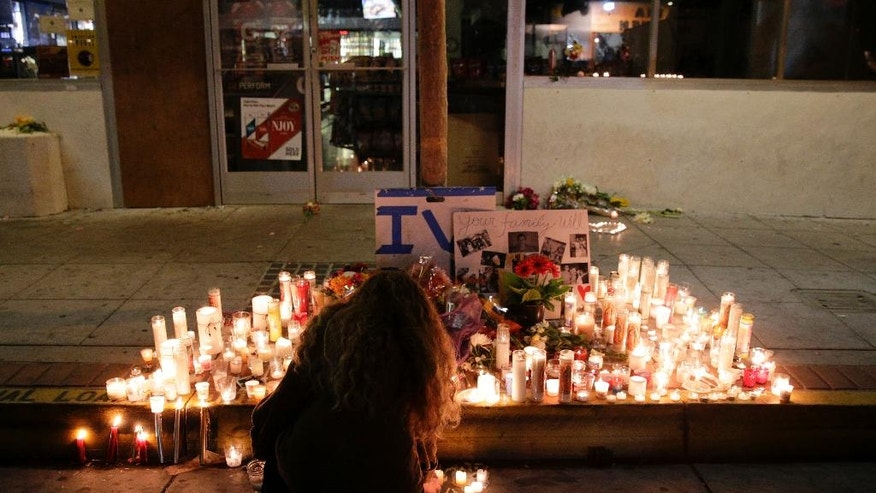A woman places a candle in front of IV Deli Mart, where par of Friday night's mass shooting took place by a drive-by shooter, on Saturday, May 24, 2014, in the beach community of Isla Vista, Calif. Sheriff's officials say Elliot Rodger, 22, went on a rampage near the University of California, Santa Barbara, stabbing three people to death at his apartment before shooting and killing three more in a crime spree through a nearby neighborhood. (AP Photo/Jae C. Hong)