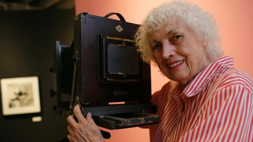 In this April 23, 2013 file photo, photographer Bunny Yeager poses with a camera similar to one used when she worked as a photographer in the 50's and 60's  at the Bunny Yeager Studio in Miami.