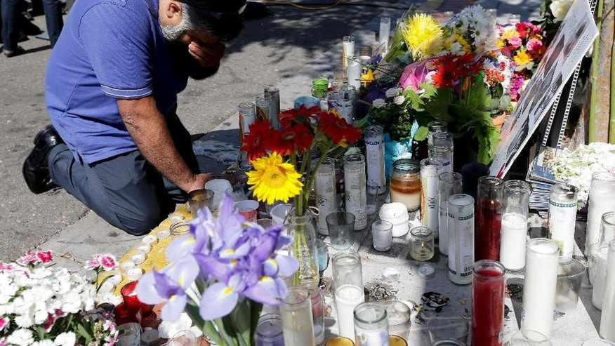 Jose Cardoso pays his respects at a makeshift memorial in front of the IV Deli Mart, where part of Friday night's mass shooting took place by a drive-by shooter Sunday, May 25, 2014, in the Isla Vista area near Goleta, Calif. Sheriff's officials said Elliot Rodger, 22, went on a rampage near the University of California, Santa Barbara, stabbing three people to death at his apartment before shooting and killing three more in a crime spree through a nearby neighborhood. (AP Photo/Chris Carlson)