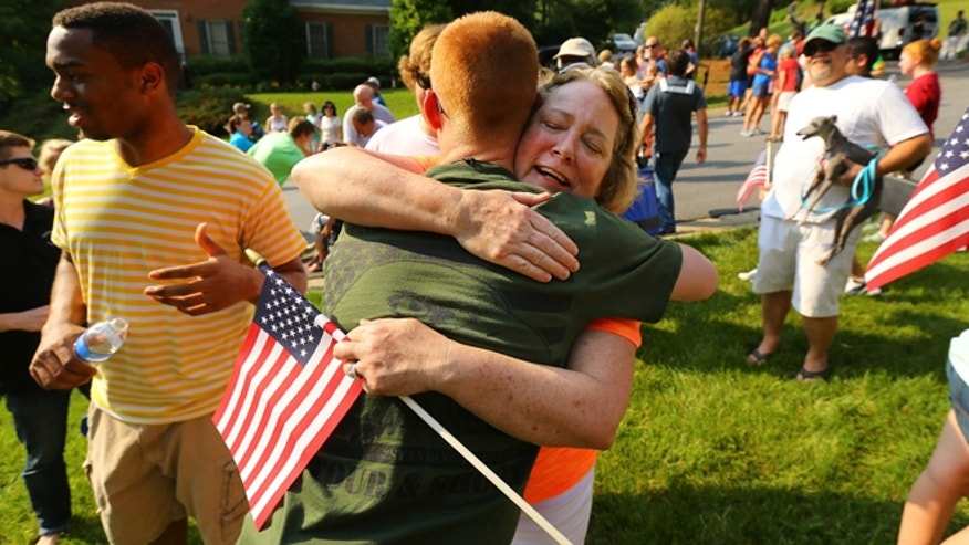 May 25, 2014: Neighbor Kathy Batton hugs Purple Heart recipient Lance Cpl. Alex Juedes, who was severely injured in Afghanistan in January of this year, as he gets a hero's welcome from friends, family and neighbors arriving home on the eve of Memorial Day in Marietta, Ga.