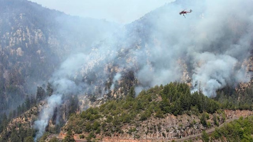 May 23, 2014: A Heavy Type-1 Skycrane Helictoper flies over the Slide Fire, above Route 89A, before dumping a 2,000 gallon load of water as it burns up Oak Creek Canyon near Flagstaff, Ariz.  The fire has burned approximately 7,500 acres and is five percent contained. (AP Photo/Ross D. Franklin)